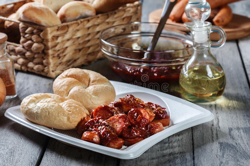 Delicious German currywurst - pieces of sausage with curry sauce stock images