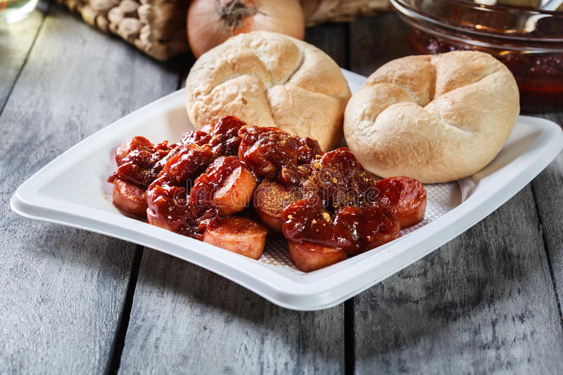 Delicious German currywurst - pieces of sausage with curry sauce stock photos