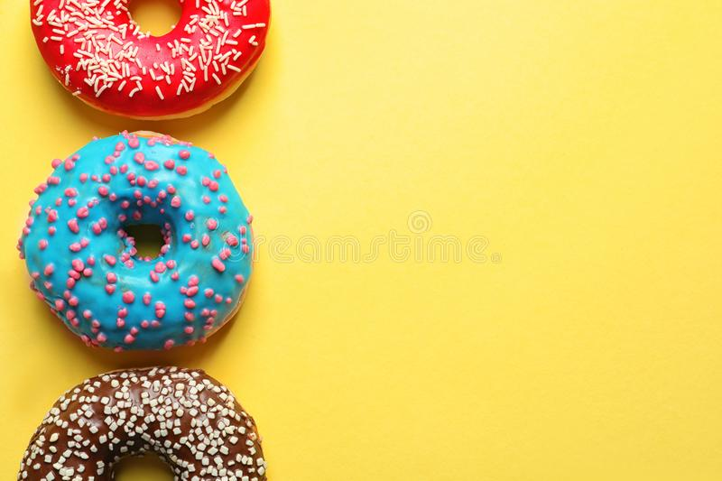 Delicious glazed doughnuts on color background. Top view stock images
