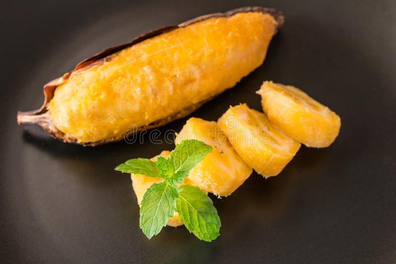 Delicious golden brown grilled banana. Grilled banana - Delicious golden brown grilled banana and slice on black plate with mint leaves. Thai dessert royalty free stock image