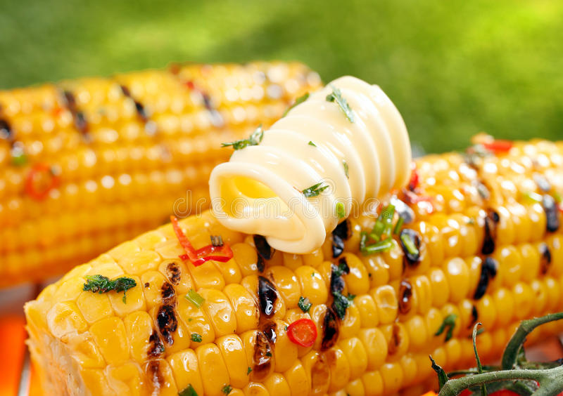 Grilled corn on the cob with butter stock images