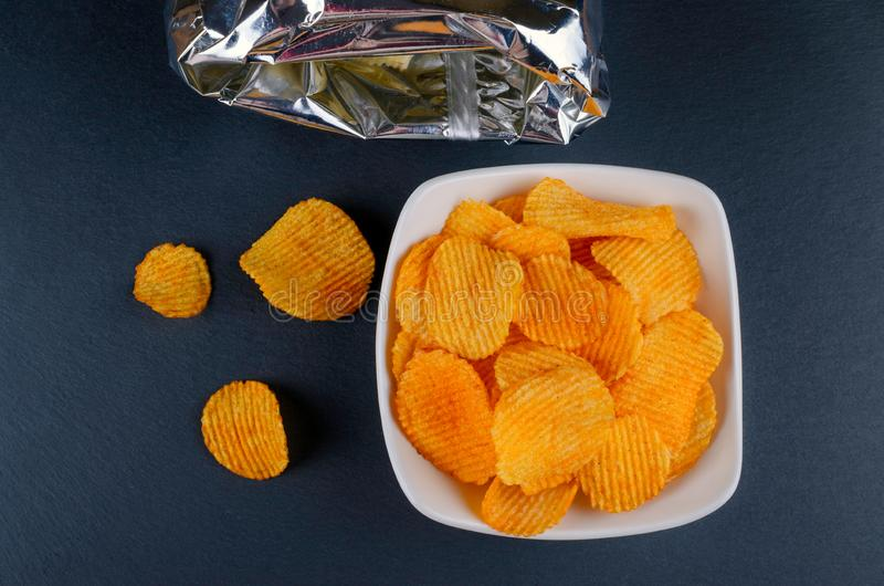 Delicious golden paprika chips in a bowl with a bag, flat lay royalty free stock photos