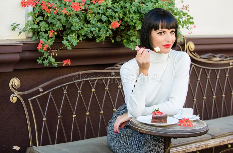 Delicious gourmet cake. Pamper yourself. Girl relax cafe with cake dessert. Woman attractive elegant brunette eat. Gourmet cake cafe terrace background. Gourmet stock image