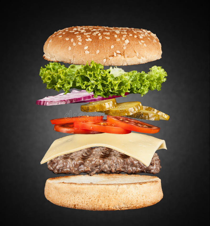 Delicious grilled burger. Burger layers on black background stock image