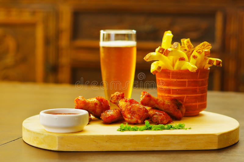 Delicious grilled chicken wings with ketchup and french fries and a glass of beer on wooden board. Delicious grilled chicken wings with ketchup, mustard and a stock photography