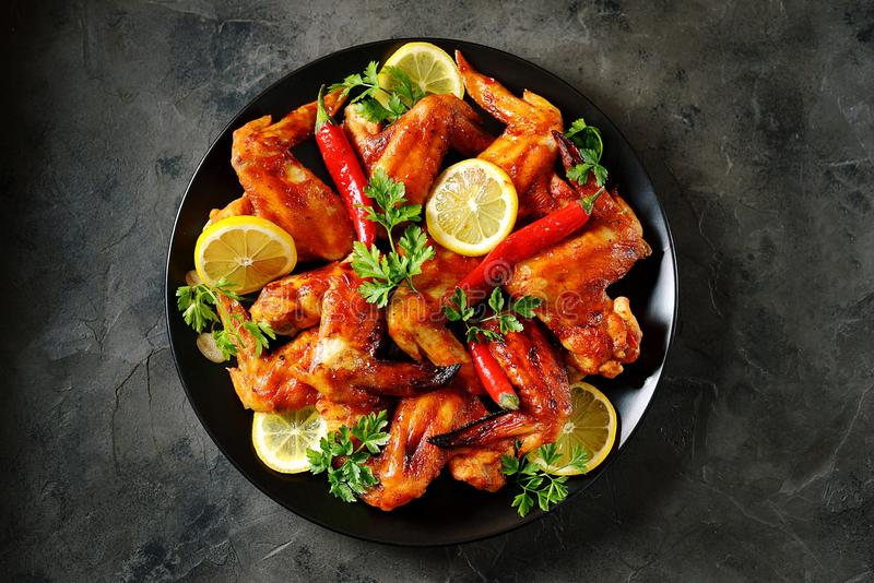 Delicious grilled chicken wings with lemon juice and chili pepper on black concrete background. Top view. Food royalty free stock image