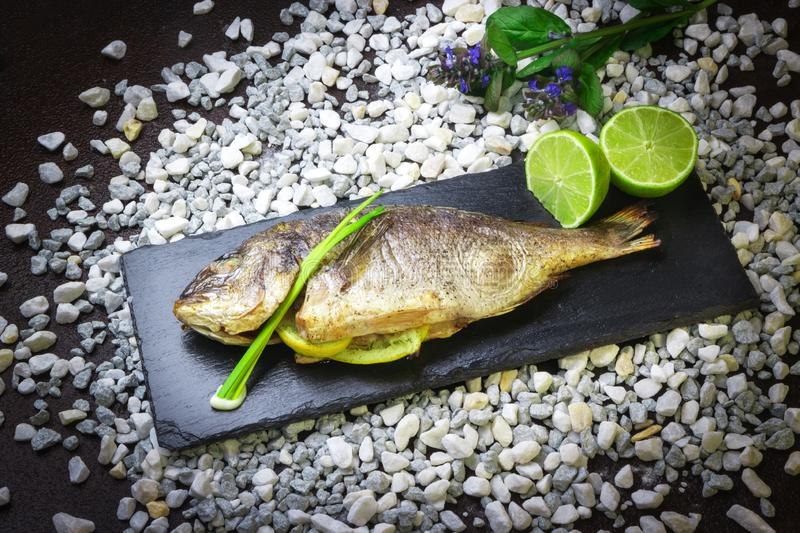 Delicious grilled dorado fish with lime and chives on a black stone plate royalty free stock photo