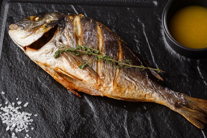 Delicious grilled dorado or sea bream fish with lemon slices, spices, rosemary on dark stone. Grilled sea fish with. Olive oil, spices and lemon ready for royalty free stock images
