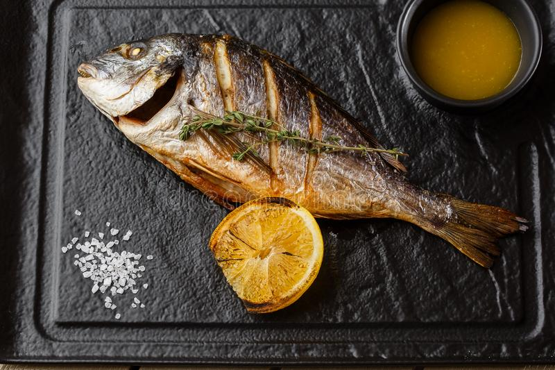Delicious grilled dorado or sea bream fish with lemon slices, spices, rosemary on dark stone. Grilled sea fish with. Olive oil, spices and lemon ready for stock photo