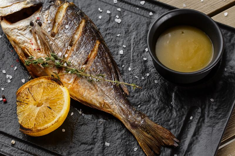 Delicious grilled dorado or sea bream fish with lemon slices, spices, rosemary on dark stone. Grilled sea fish with. Olive oil, spices and lemon ready for royalty free stock photo