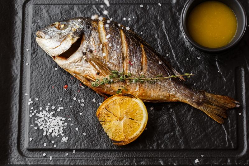 Delicious grilled dorado or sea bream fish with lemon slices, spices, rosemary on dark stone. Grilled sea fish with. Olive oil, spices and lemon ready for royalty free stock photos