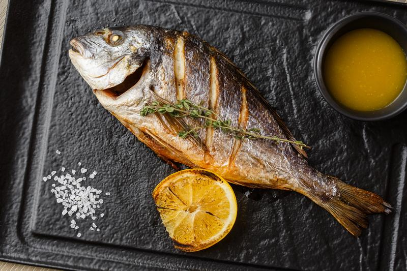 Delicious grilled dorado or sea bream fish with lemon slices, spices, rosemary on dark stone. Grilled sea fish with. Olive oil, spices and lemon ready for stock images