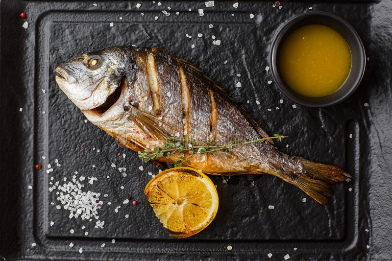 Delicious grilled dorado or sea bream fish with lemon slices, spices, rosemary on dark stone. Grilled sea fish with. Olive oil, spices and lemon ready for stock image