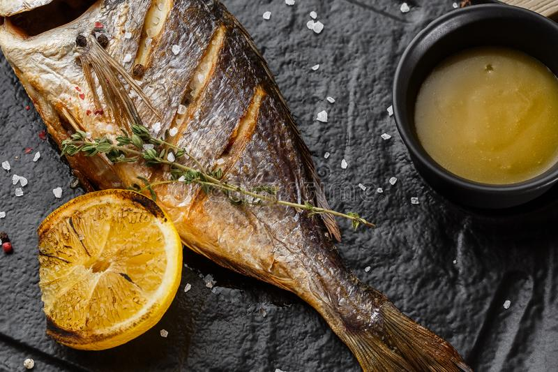 Delicious grilled dorado or sea bream fish with lemon slices, spices, rosemary on dark stone. Grilled sea fish with. Olive oil, spices and lemon ready for royalty free stock photography
