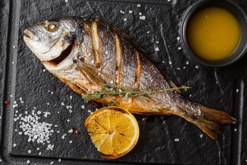 Delicious grilled dorado or sea bream fish with lemon slices, spices, rosemary on dark stone. Grilled sea fish with. Olive oil, spices and lemon ready for royalty free stock image