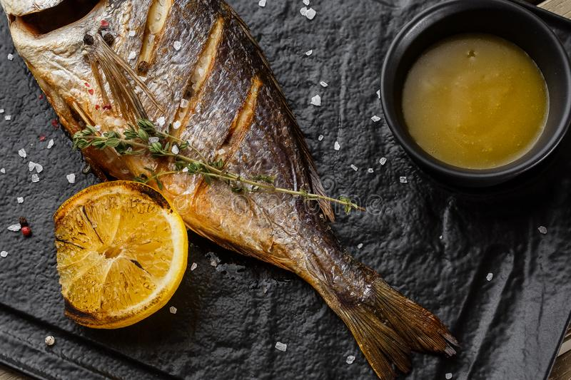 Delicious grilled dorado or sea bream fish with lemon slices, spices, rosemary on dark stone. Grilled sea fish with. Olive oil, spices and lemon ready for stock photos