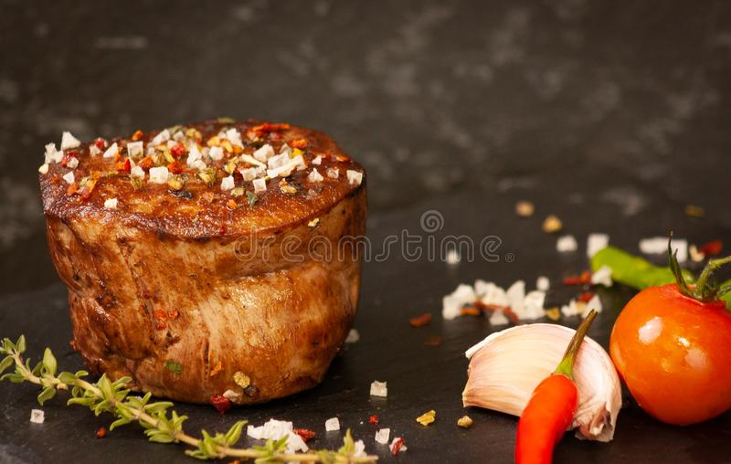 Delicious grilled beef filet with green asparagus. Delicious grilled beef filet with tomato, Chili Peppers and garlig royalty free stock images