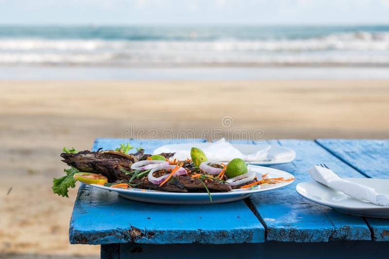 Delicious grilled fish on blue table. Ocean waves on background. stock photography