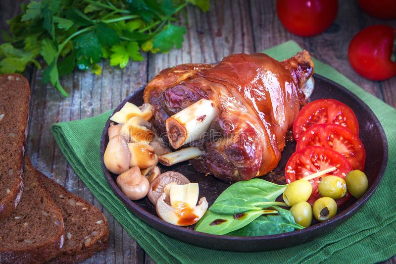 Delicious grilled pork knuckle with fresh vegetables and pickled mushrooms. Delicious food stock photos