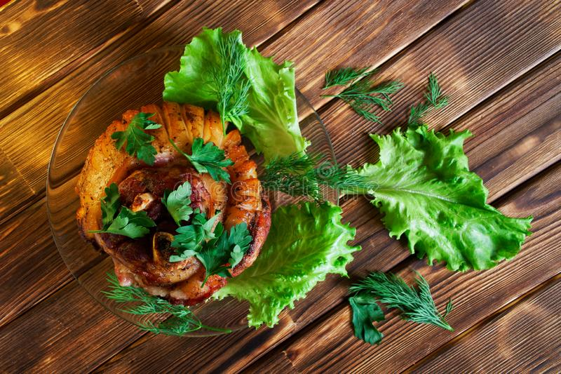 Delicious grilled pork knuckle in a transparent plate next to parsley, lettuce and dill. Baked meat lies on a wooden rustic table royalty free stock image