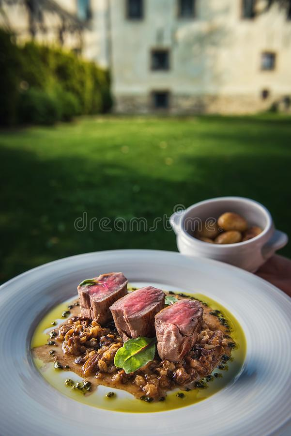 Delicious grilled pork loin with mushrooms sauce served on white plate with grilled potatoes, modern gastronomy, product photograp. Hy for restaurant stock images
