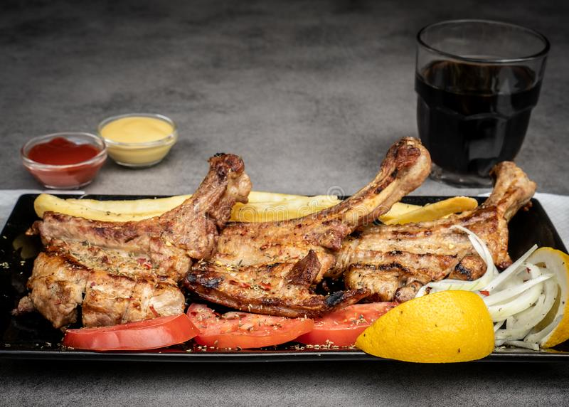 Delicious Grilled Pork Steak served with fried potatoes, fresh tomatoes, onions and lemon stock photography