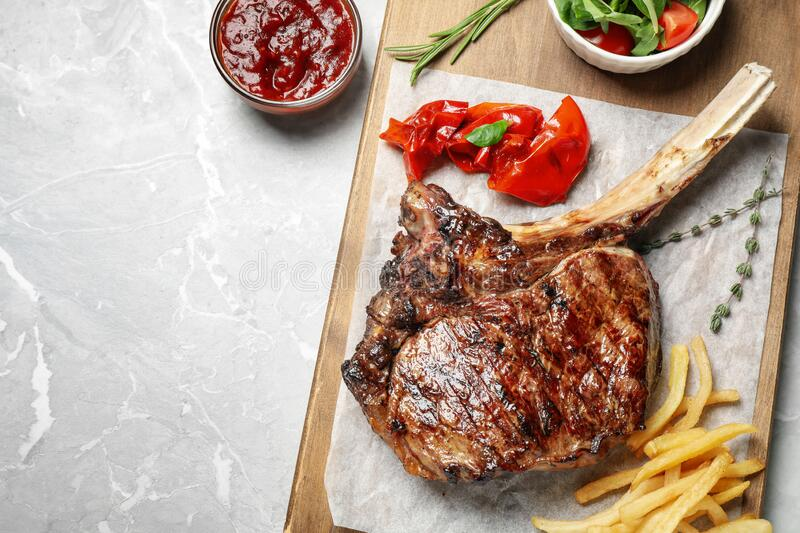 Delicious grilled ribeye steak served on light grey marble table, flat lay. Space for text. Delicious grilled ribeye steak served on light grey marble table stock photo