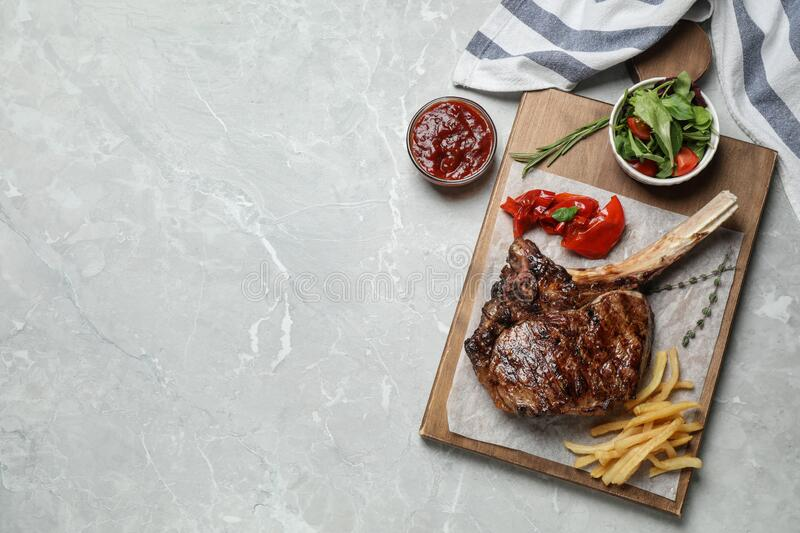Delicious grilled ribeye steak served on light marble table, flat lay. Space for text. Delicious grilled ribeye steak served on light grey marble table, flat lay stock photography