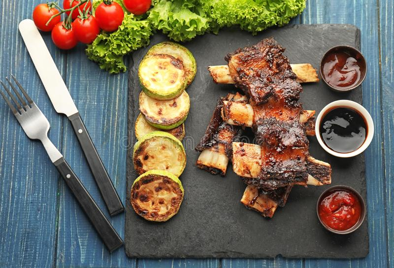 Delicious grilled ribs with different sauces and squash on slate plate stock photography