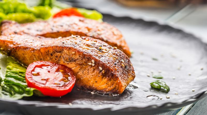 Delicious grilled roasted salmon fillets or steaks with sesame tomatoes and lettuce salad.  stock images