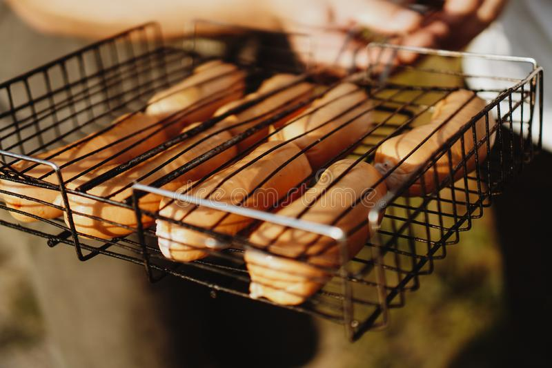 Delicious grilled sausages resting on the iron grid of a portable barbecue royalty free stock photos