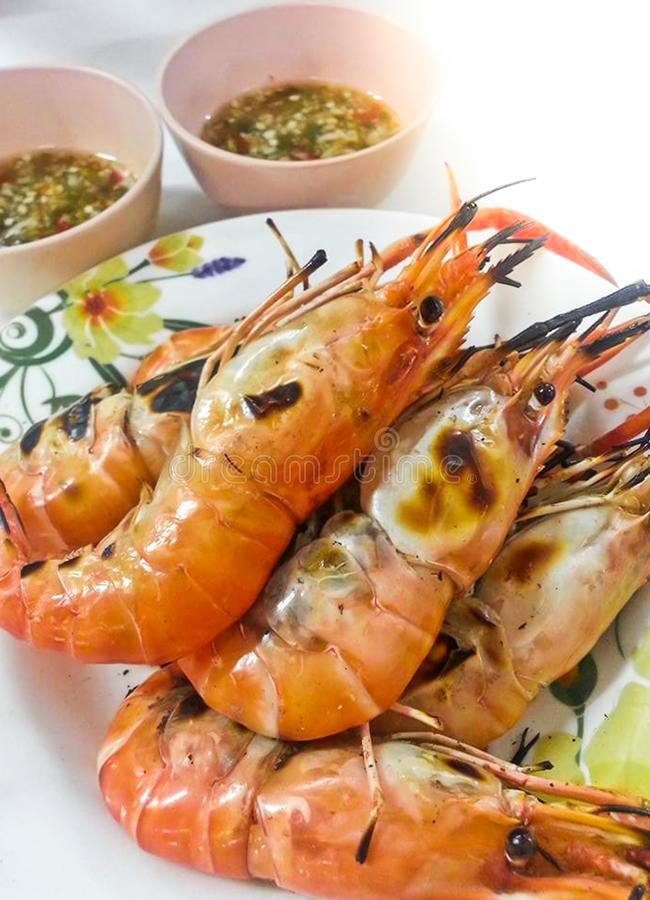 Delicious Grilled shrimps Fresh Prawns on white plate with seafood sauce. View from above stock image