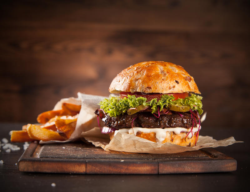 Delicious hamburger on wood. Delicious hamburger served on wooden planks royalty free stock images