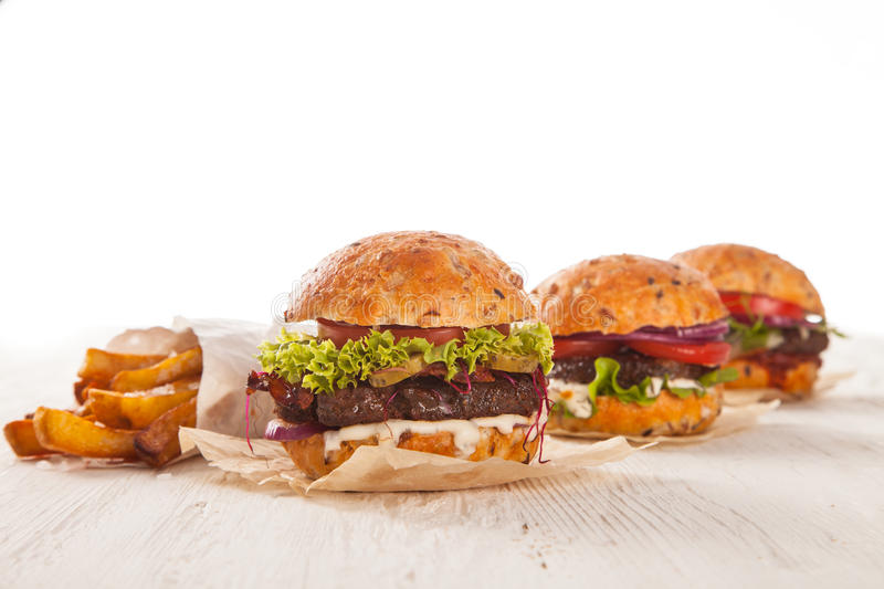 Delicious hamburger on wood. Delicious hamburger served on wooden planks royalty free stock photography