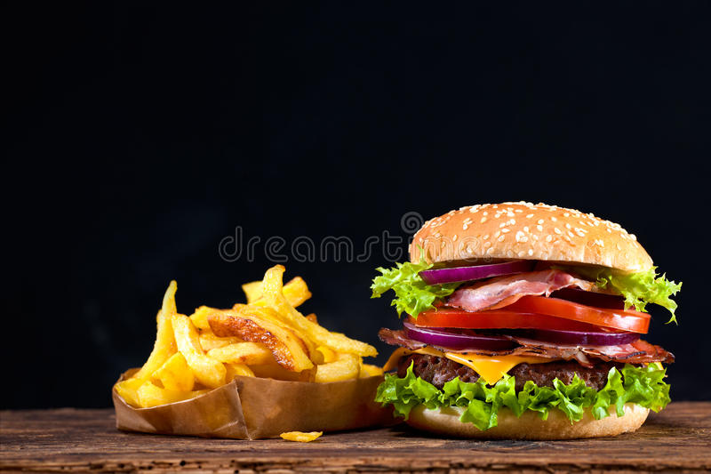 Delicious hamburger on wooden table. Delicious hamburger with french fries on wooden table stock image