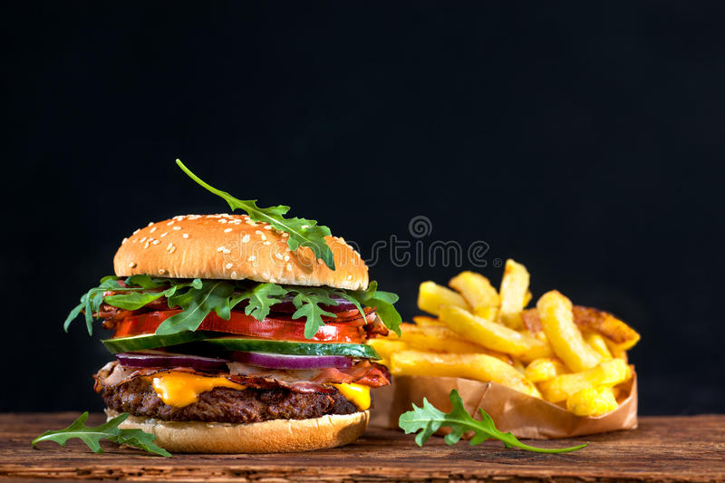 Delicious hamburger on wooden table. Delicious hamburger with french fries on wooden table royalty free stock image