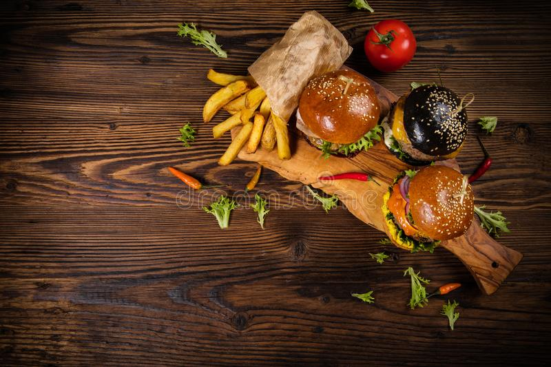 Delicious hamburgers with fries, served on wood stock photography