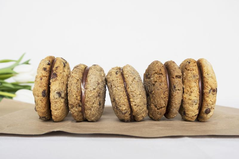 Delicious hazelnut or almond sandwich biscuits with chocolate, ganache and gianduja filling. Baci di dama. Tasty hazelnut or almond sandwich biscuits with stock images