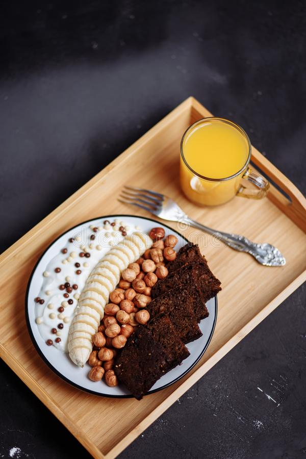 Delicious healthy Breakfast in the morning. Rye bread, banana, hazelnut, chocolate muesli, yogurt and fresh orange juice stock photography