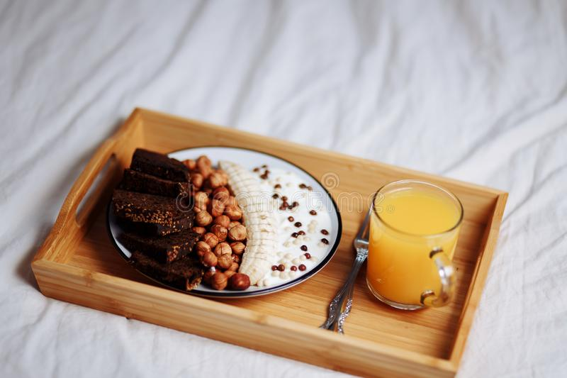 Delicious healthy Breakfast in the morning. Rye bread, banana, hazelnut, chocolate muesli, yogurt and fresh orange juice in a royalty free stock photography