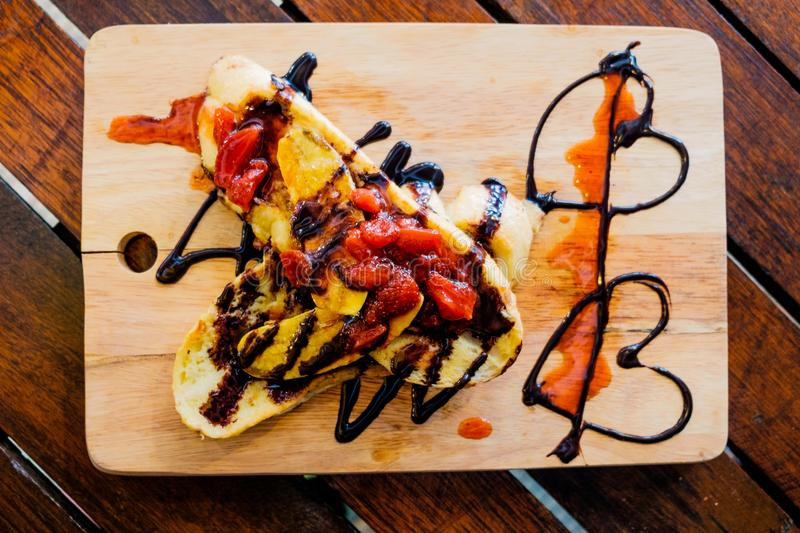 View from above of tasty pancake with melted chocolate and strawberries with warm morning light on wood table royalty free stock image