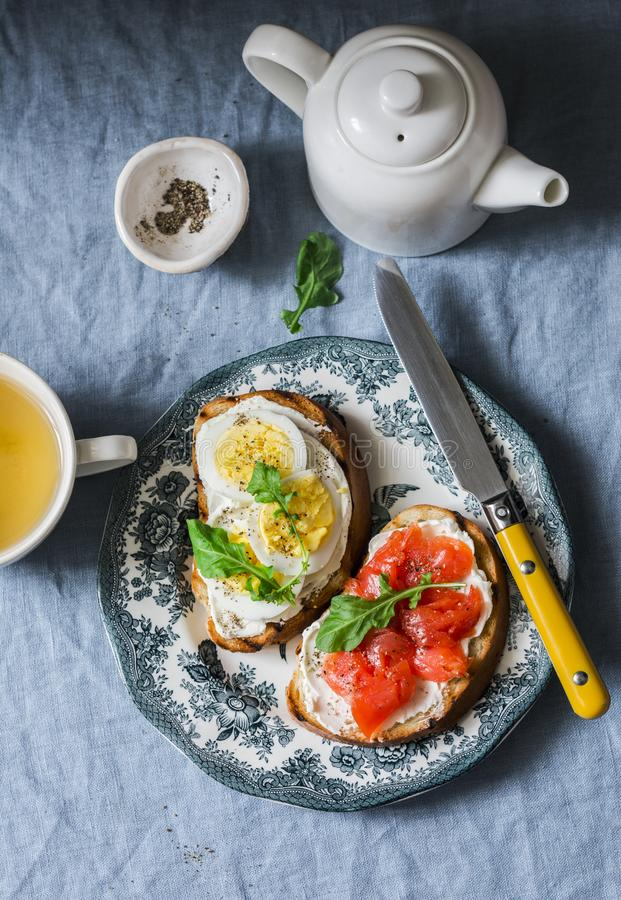 Delicious healthy breakfast or snack - sandwiches with cream cheese, boiled egg and smoked salmon and green tea on a blue backgrou stock photo