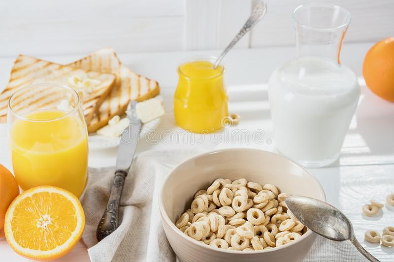 Delicious Healthy breakfast. Whole Grain Cereal rings, milk, honey and orange juice on the white table. Cheerios whole grain cere stock image