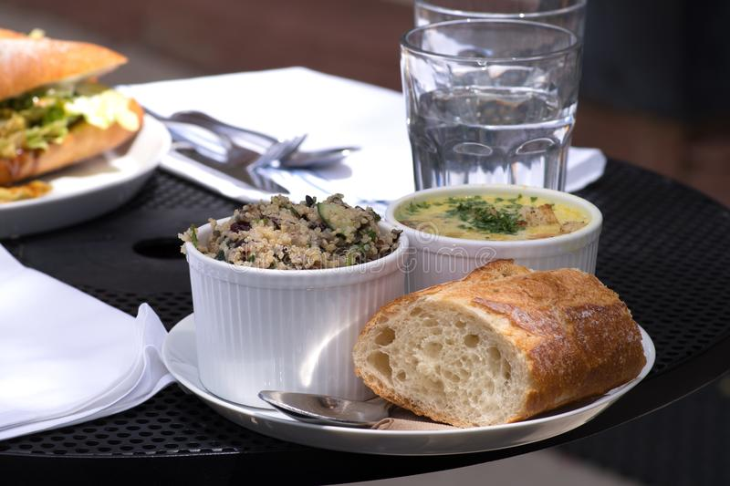 Delicious and healthy combo lunch with quinoa salad, fresh baguette and soup. stock photography
