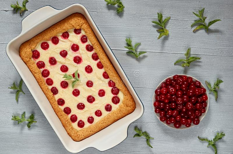 Delicious healthy dessert - cherry pie in the baking dish on the gray kitchen background. Homemade summer cheesecake. Decorated with raw ingredients - cherries stock photos