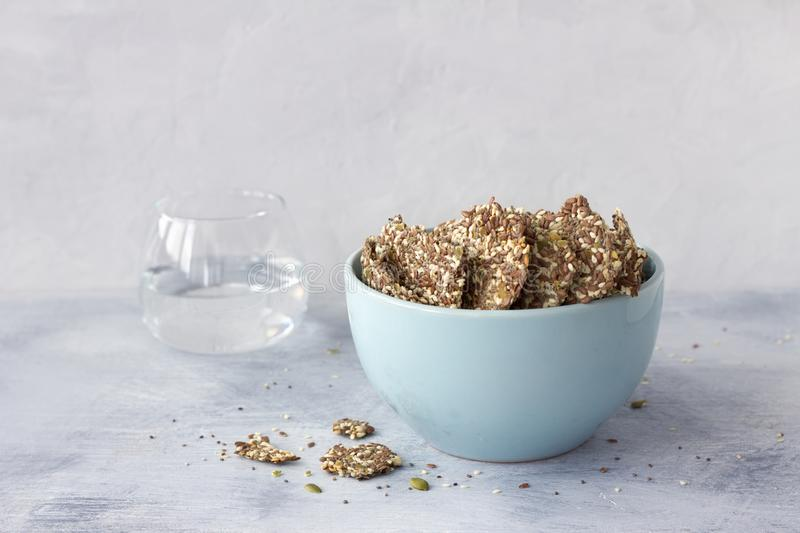 Healthy multigrain gluten-free crackers, ketogenic, from chia seeds, flax, sesame and ground pumpkin seeds in ceramic bowl stock photos