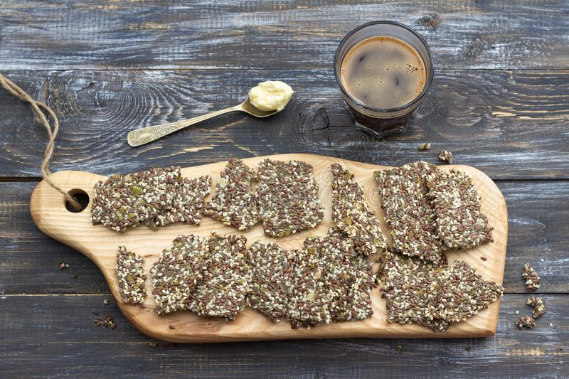 Delicious healthy multigrain gluten-free crackers, ketogenic and keto coffee in glass with spoon of butter stock images