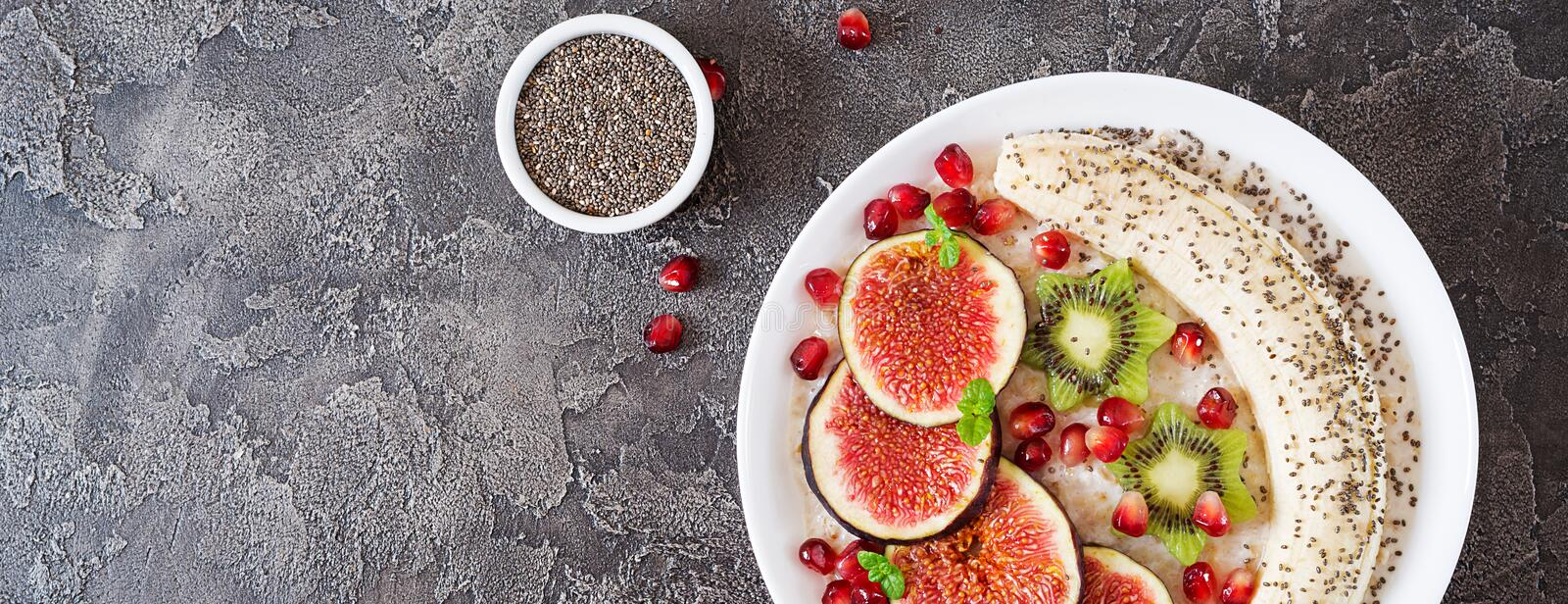 Delicious and healthy oatmeal with figs, kiwi, pomegranate, banana and chia seeds. Healthy breakfast. Fitness food. Proper. Nutrition. Flat lay. Banner. Top royalty free stock photo