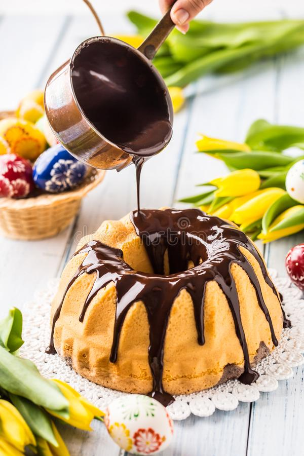 Delicious holiday slovak and czech cake babovka with chocolate glaze. Pouring chocolate topping. Easter decorations - spring royalty free stock image