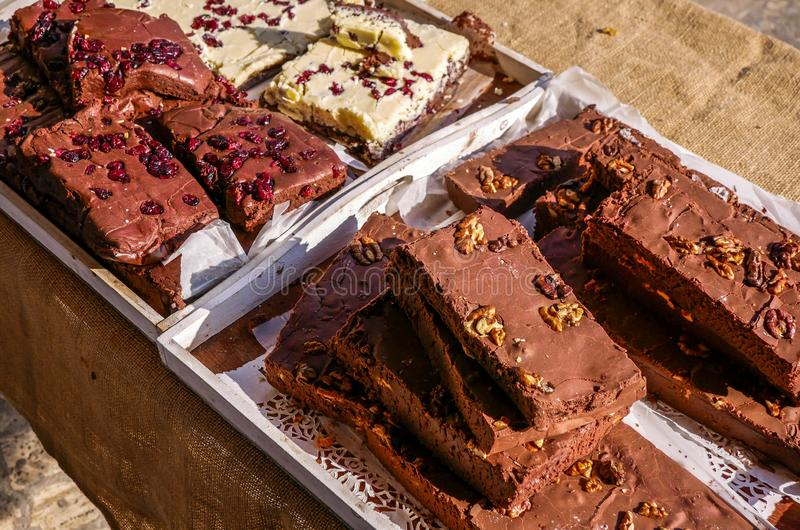 Delicious home baked brown chocolate bars with walnut  and pomegranate seeds. Close up shot at the local fair royalty free stock image